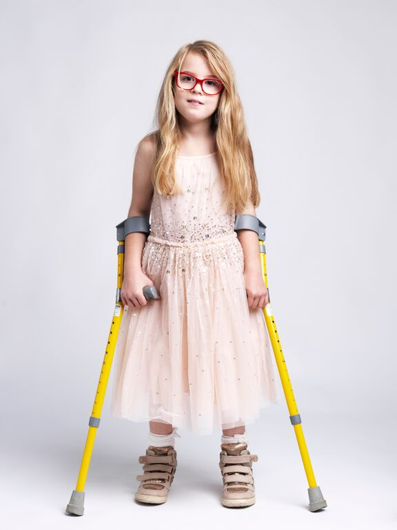 emily in pink dress with crutches