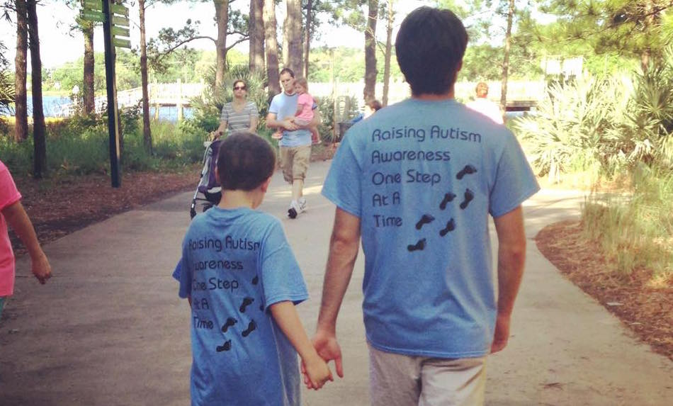 Two brothers walking hand in hand at the zoo both wearing t-shirts that read Raising Autism Awareness One Step At A Time