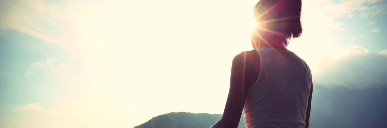 young yoga woman sit meditation on sunrise mountain peak rock