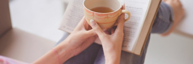 hands holding a teacup in front of an open book