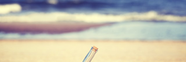 Vintage toned message in a bottle on beach, shallow depth of field.