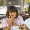 Woman laughing behind hand sitting at table with friend
