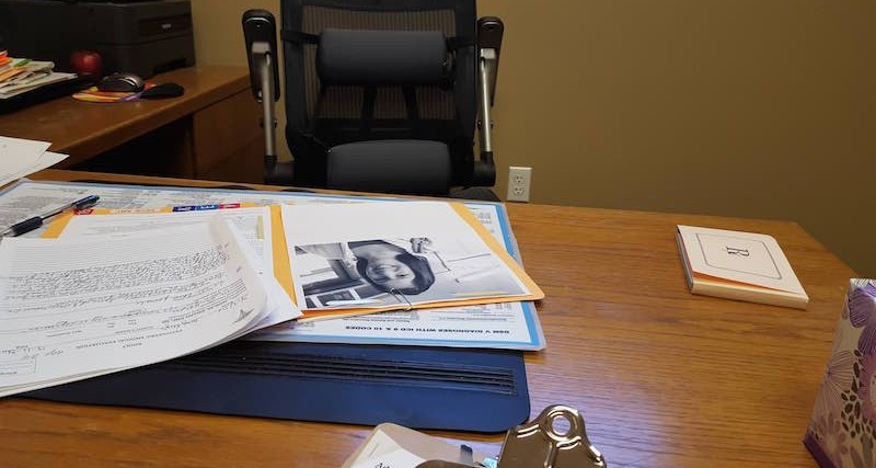 therapist's desk with papers and files on it and chair behind