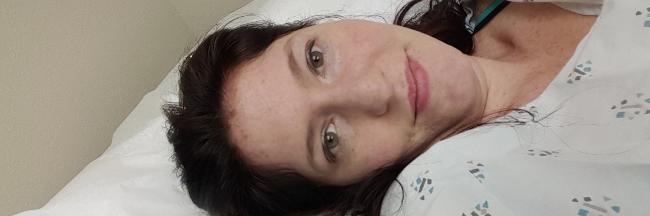 woman lying on bed wearing hospital gown