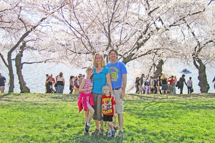 family standing together on green grass under cherry trees