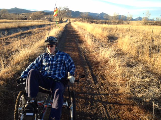 Gary riding his trike on a trail through the prairie.