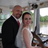 bride and groom in wedding outfits steering boat