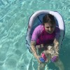 woman seated in pool chair in the water holding two small toys