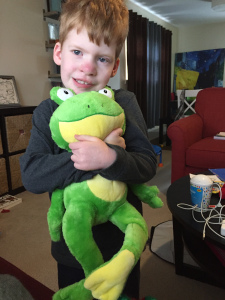 young boy holding stuffed frog to his chest
