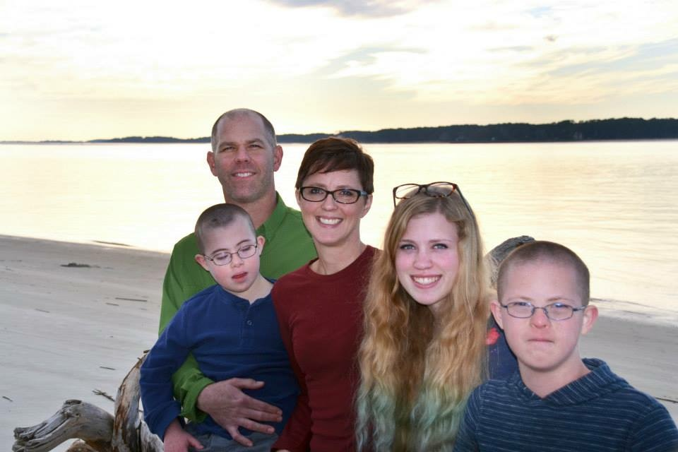 family photo in front of a lake
