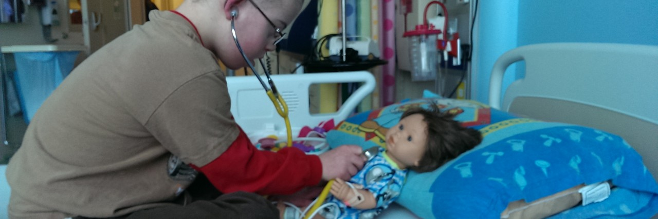 boy playing doctor with doll
