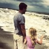 father and daughter holding hands standing on the beach looking at the waves