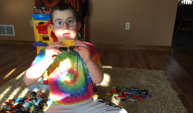 boy in tie-dye shirt playing with toy cars
