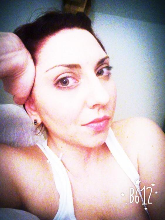 woman's selfie wearing a white tank top