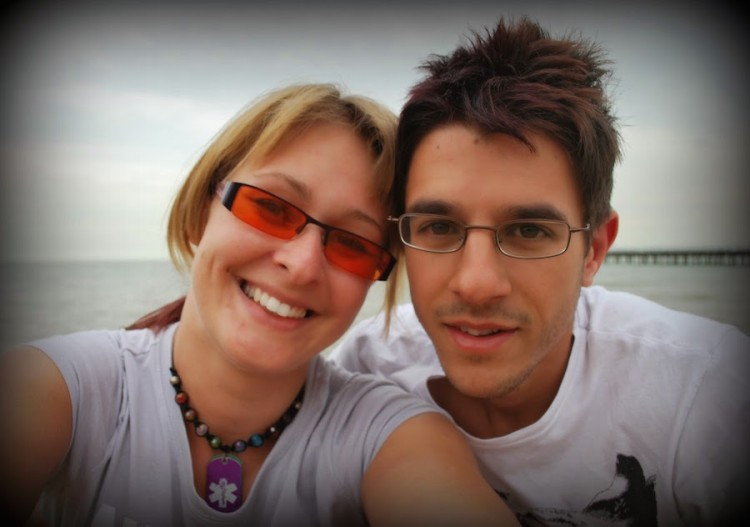 man and woman smiling in front of water