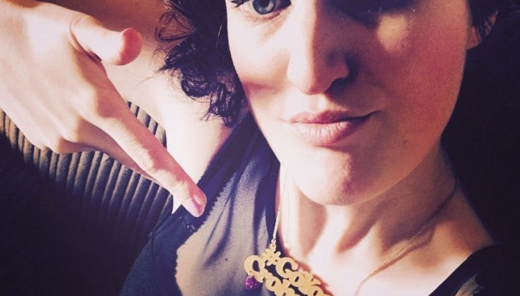 woman pointing to necklace that says Go Your Crohn Way