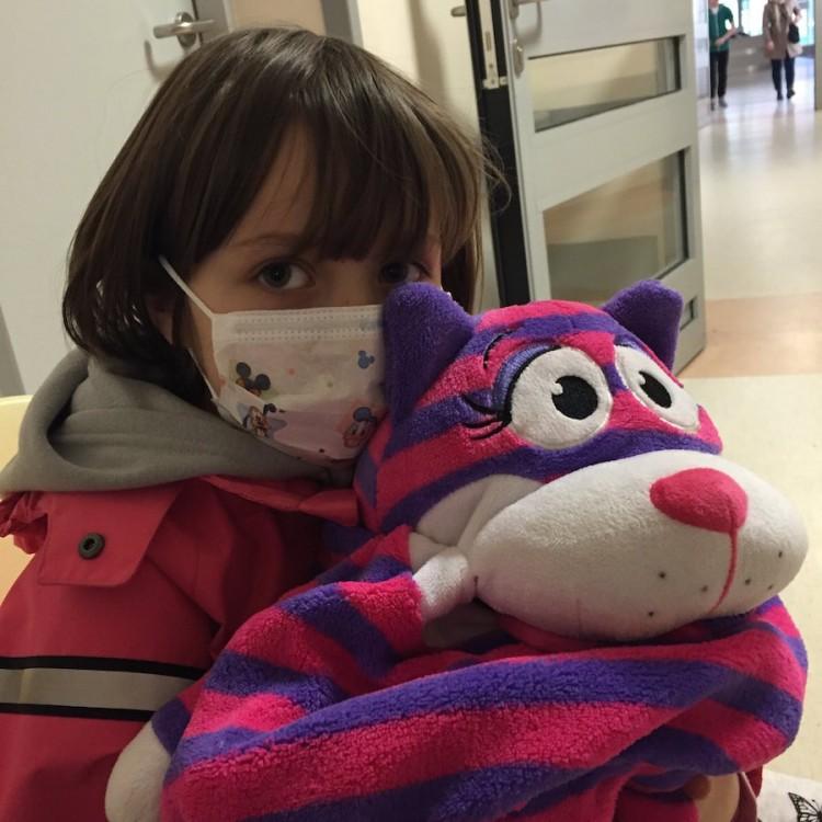 girl wearing hospital mask holding pink and purple stuffed animal