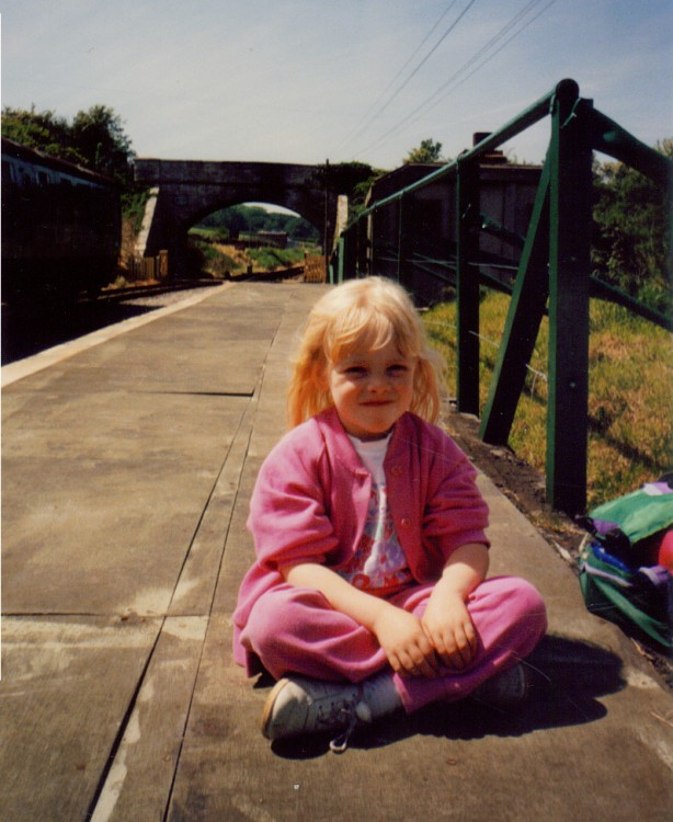 a young girl in a pink outfit sitting on a bridge