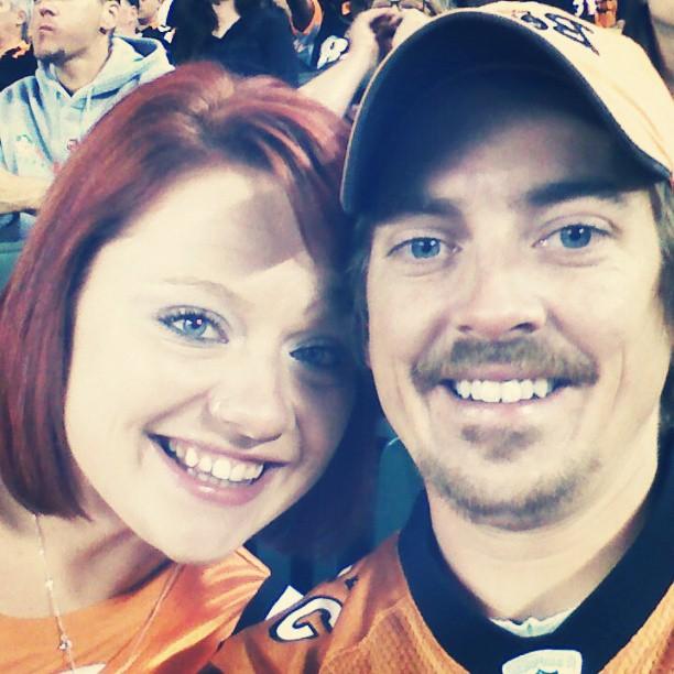 man and woman at game wearing orange jerseys