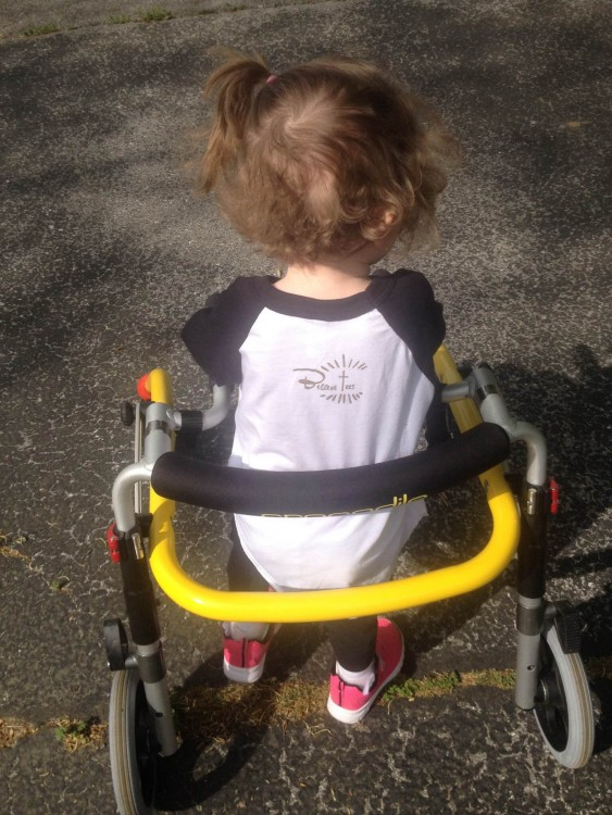 Alana's daughter with her yellow gait trainer and pink shoes