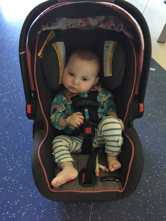 baby sitting in car seat on the floor
