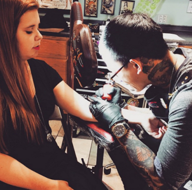 young woman sitting in tattoo parlor getting a tattoo on her arm