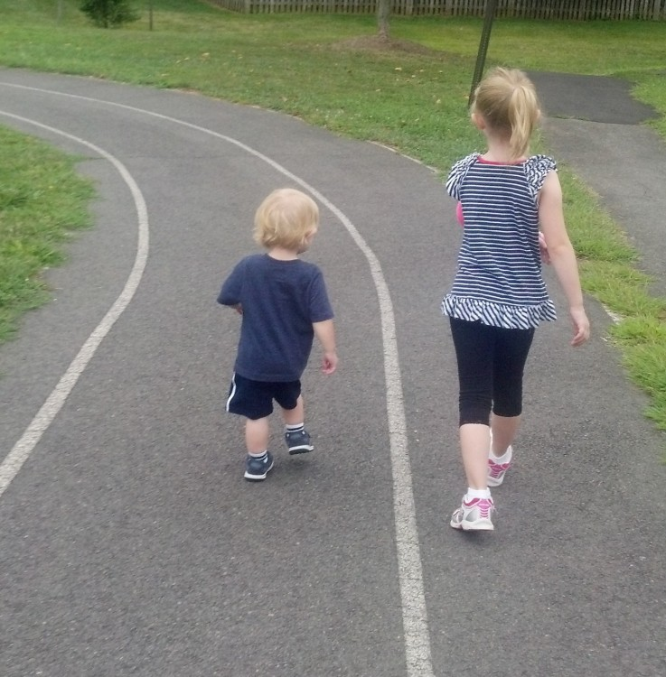 two kids running on a path with grass on each side