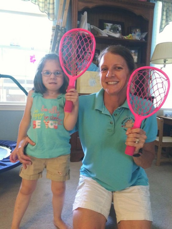 Mother and daughter holding pink rackets.