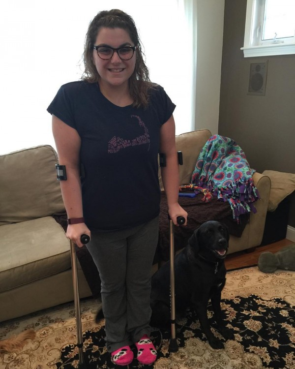 woman standing in front of couch with crutches next to black dog
