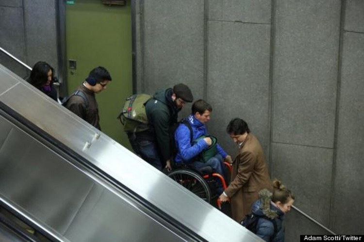 Justin Trudeau helps a man in a wheelchair down a flight of stairs.