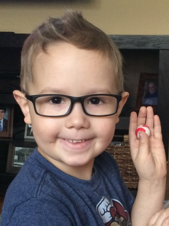 little boy in glasses holding up a small toy
