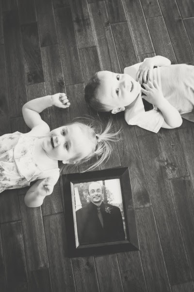 A little boy and girl lay on the floor with a framed picture of a man.
