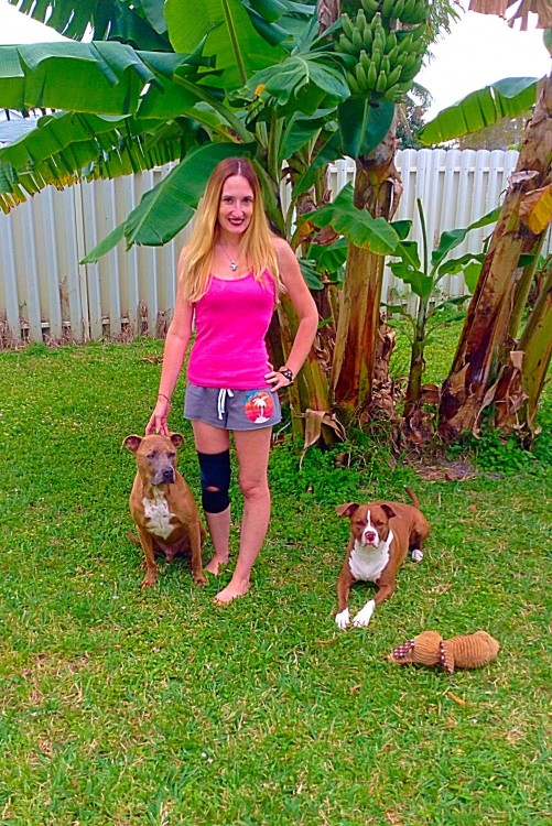 woman standing in a yard with her dogs