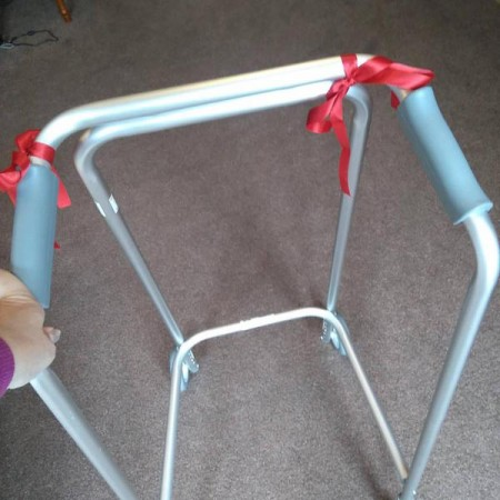 anne's zimmer frame used for walking and balance. two red bows are tied to it.