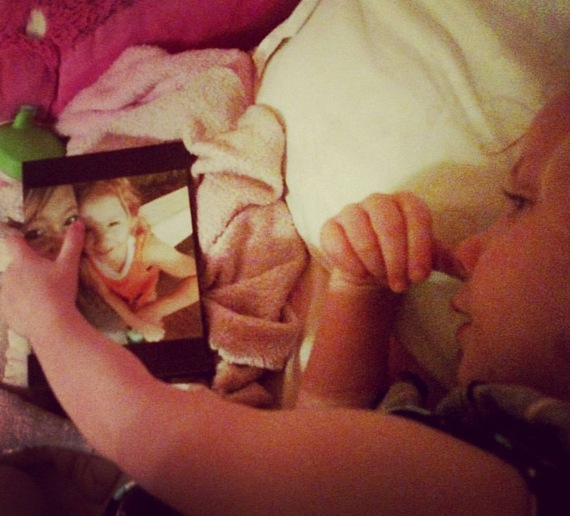 young girl lying in bed looking at frame photo of her with her mother