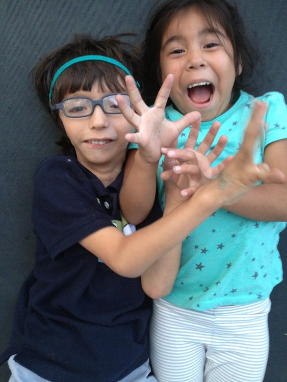 Joel and his sister smiling and reaching their hands out.