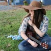author with hat on playing guitar