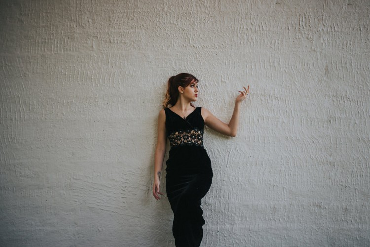 Ashley standing alone against a white wall looking and gesturing to the right