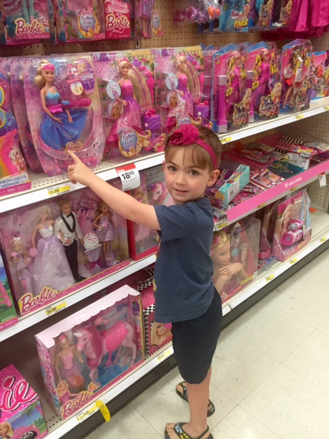 author's son picking out barbie doll