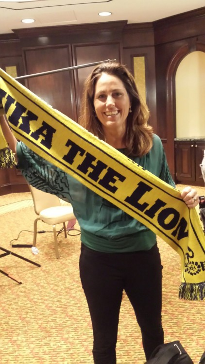 Julie Foudy holding the Luka the Lion scarf.