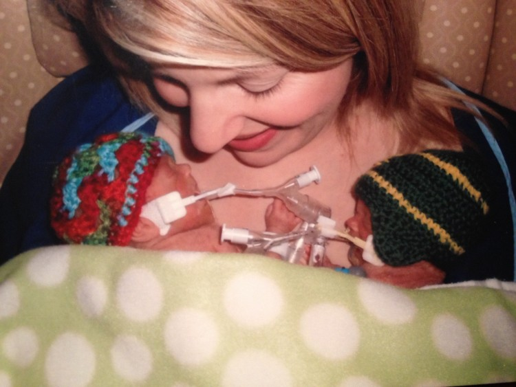 a mother holding two preemies in her arms