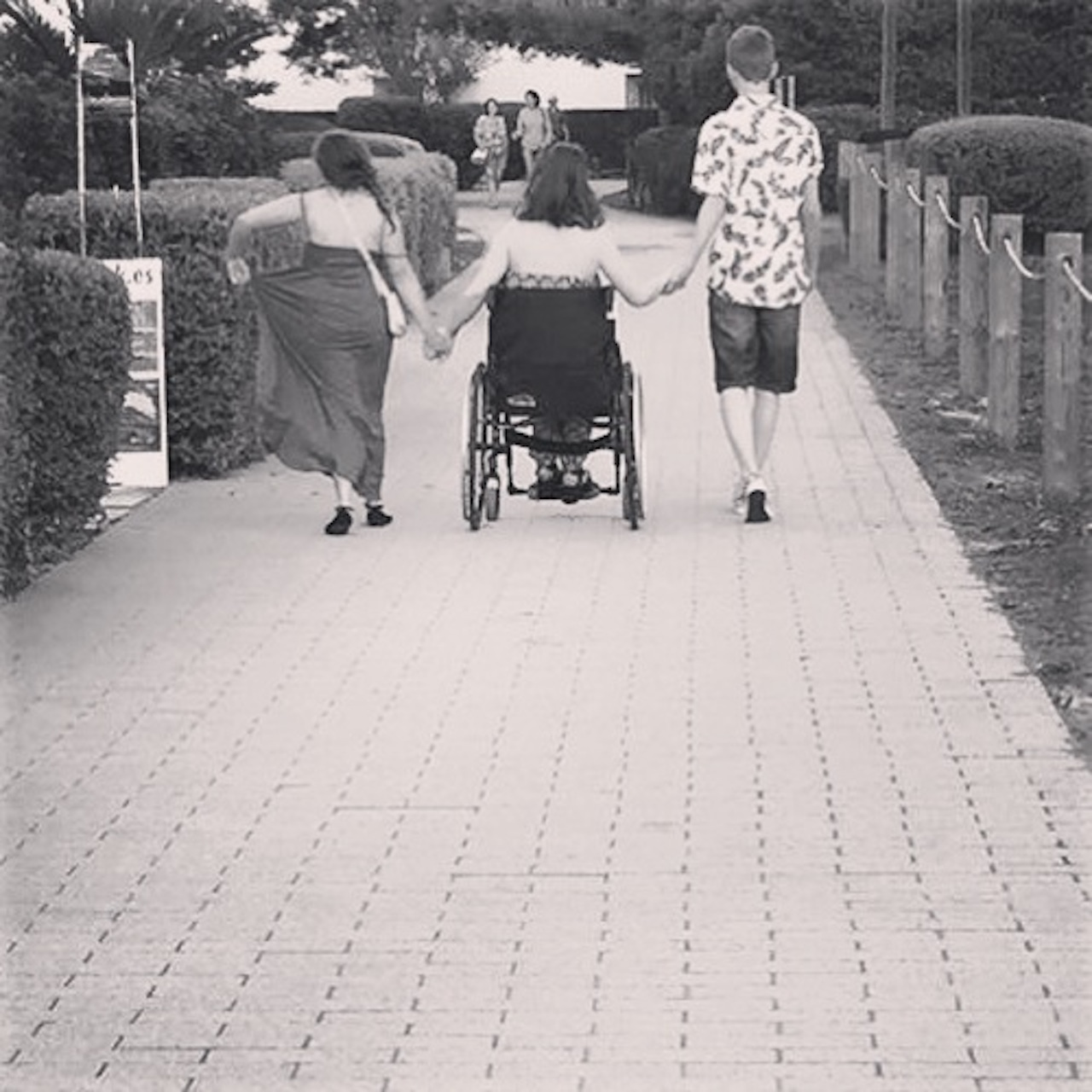 woman in wheelchair holding two friends' hands