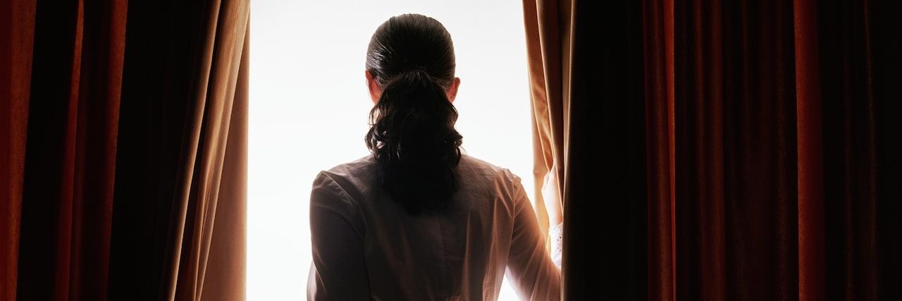 Woman staring through curtains