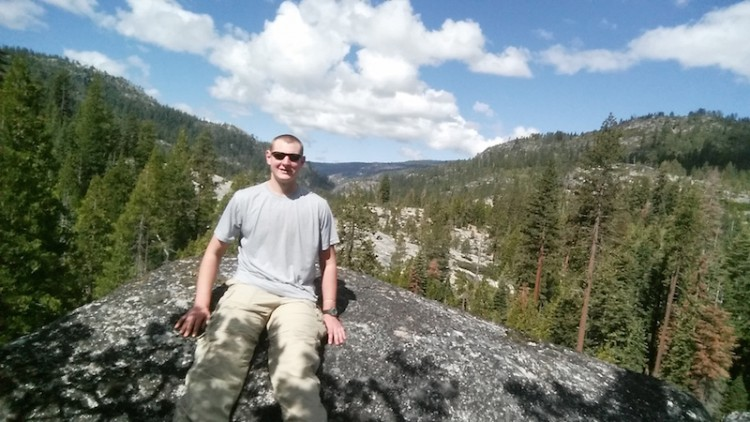 man sitting on rock with mountain view behind him