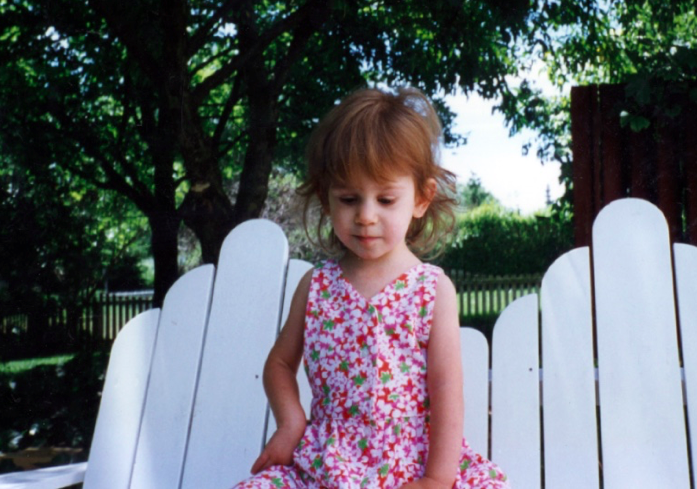 Sera at two years old sitting on a bench in a dress.