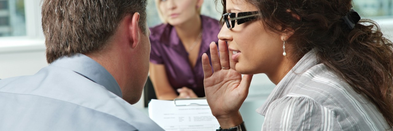 a woman whispering to a man in front of their coworker