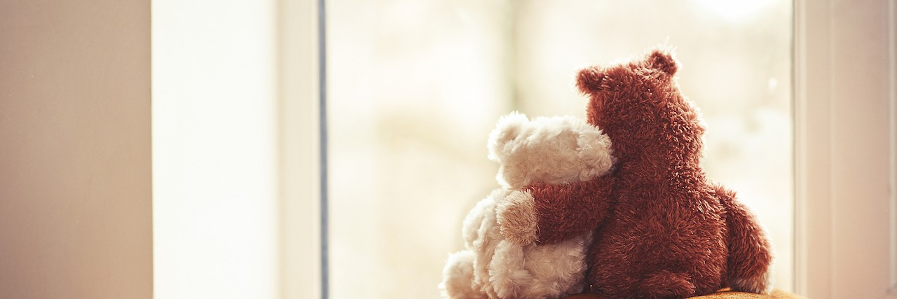 Two embracing teddy bears looking through the window sitting on window-sill.