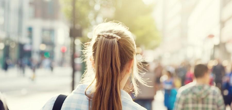 back of woman's head as she walks down street