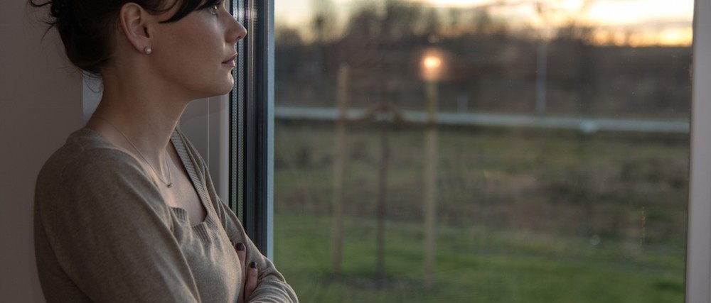 Desolate young woman looking sad out of the window