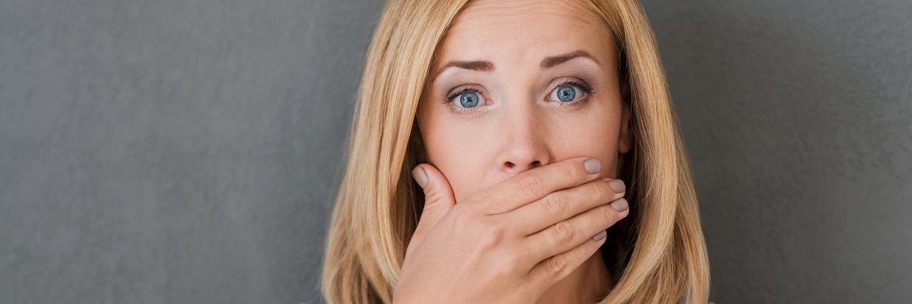 Surprised woman covering mouth with hand and staring at camera while standing against grey background